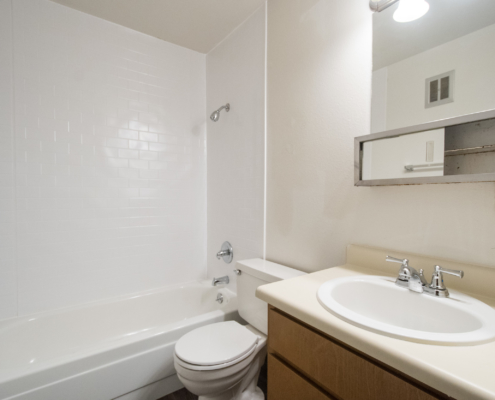 A picture showing the bathtub/shower, toilet, and sink in the bathroom